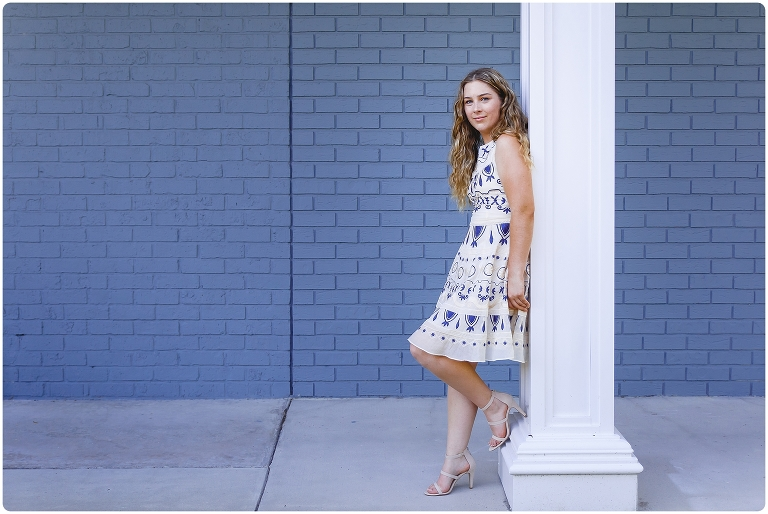 Senior Portrait in Sarasota of girl in blue and white dress in front of a blue brick wall